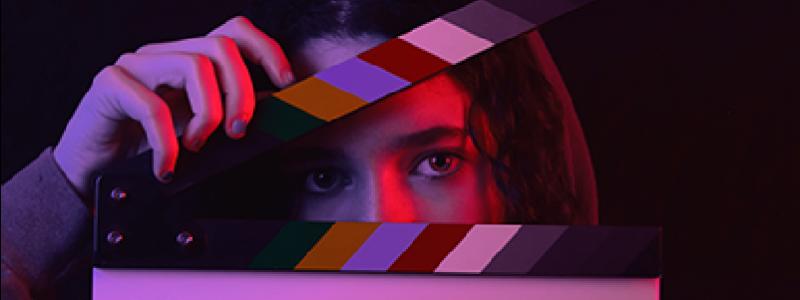 Person mit einer Filmklappe vor dem Gesicht